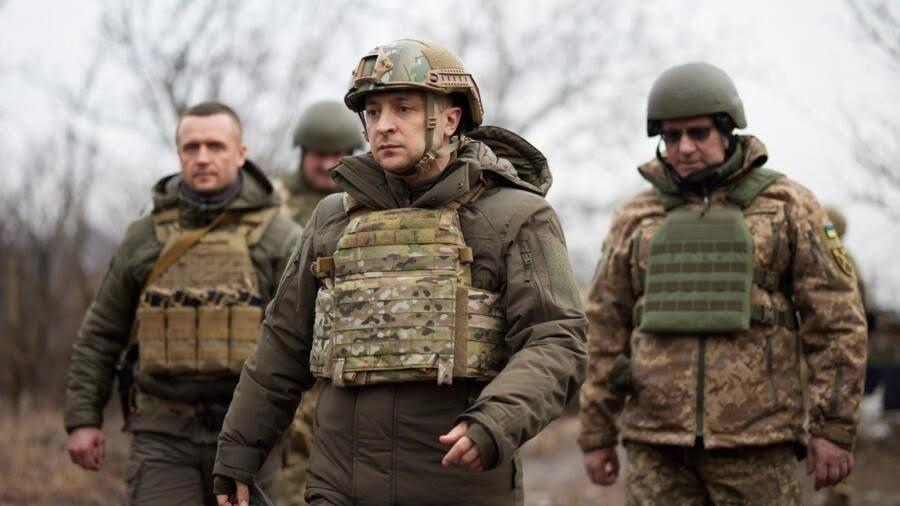 Ukrainian President Volodymyr Zelenskiy, centre, surrounded by servicemen as he visits the war-hit Donetsk region, eastern Ukraine, on February 11, 2021.