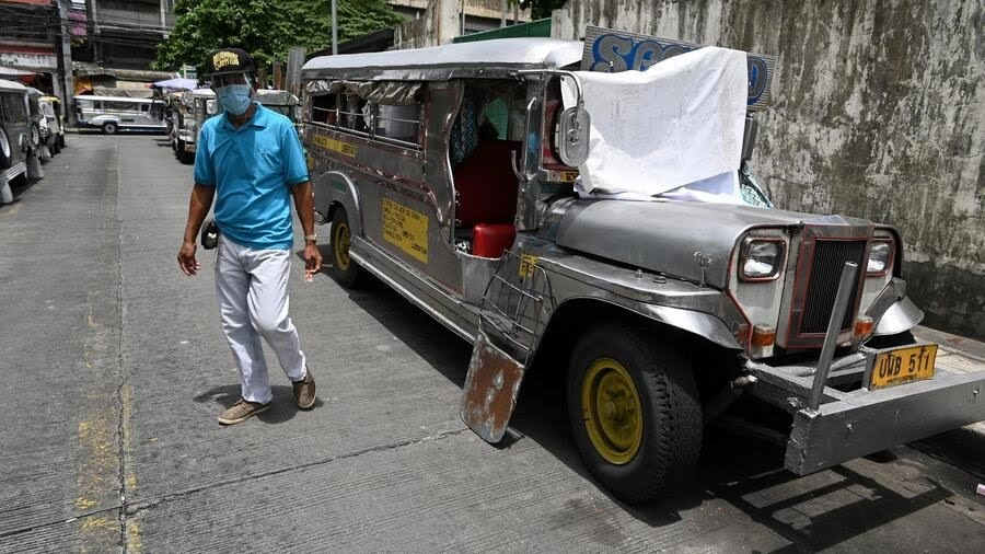 A resident walks past jeepneys serving as temporary homes parked along a road in Manila